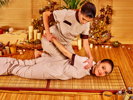 thai yoga: Therapist giving stretching massage to woman.