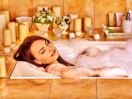 bathtub: Woman relaxing at water in bubble bath.