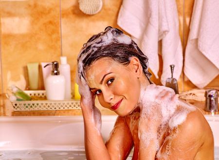 Happy woman washing hair in bubble bath.