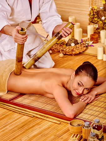 bamboo stick: Young woman getting bamboo stick massage of male therapist. Stock Photo