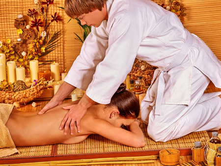 male massage: Young woman getting bamboo massage. Male therapist kneels.