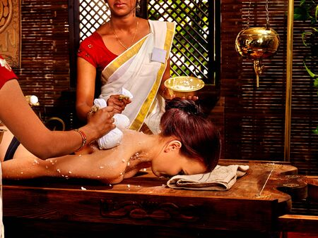 panchakarma: Woman and two masseuses having Indian massage with pouch of rice. Stock Photo