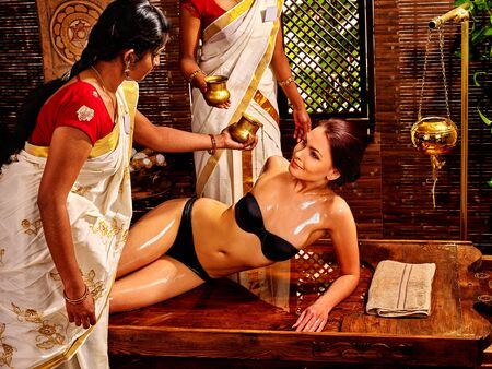panchakarma: Young woman having pouring oil Ayurveda spa treatment. Stock Photo