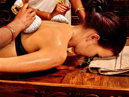 panchakarma: Woman having Ayurveda massage with pouch of rice. Not visible face.