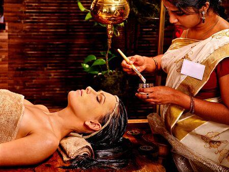 indian mask: Woman with closed eyes having facial mask at ayurveda spa. Stock Photo