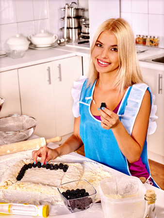 woman baking: Young woman  baking cookies with berry in oven. Stock Photo