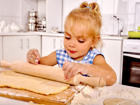 preparing dough: Child little girl with rolling-pin preparing dough at kitchen. Stock Photo