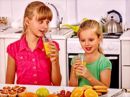 niños desayunando: Niños felices del desayuno en la cocina. Niños potable fresca de naranja.