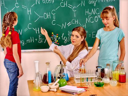 niños sentados: Profesor con los niños sentados en la mesa en clase de química.