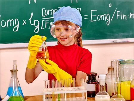 chemistry lesson: Child in hat holding flask in chemistry class. Stock Photo