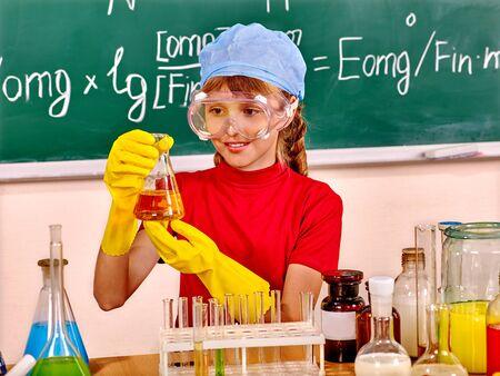 qu�mica: Ni�o en el sombrero frasco sosteniendo en la clase de qu�mica.