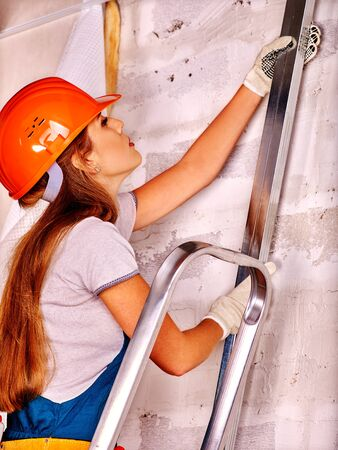 foremaster: Happy working woman in builder uniform indoor. Stock Photo