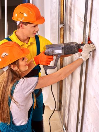 foremaster: Happy woman working  and man in builder uniform indoor.