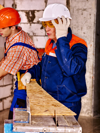 circular saw: Group people  builder and old man with circular saw. Stock Photo