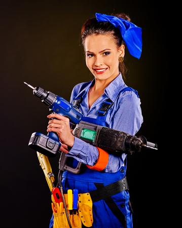 outils construction: Femme heureuse constructeur tenant des outils de construction. Fond noir. Banque d'images