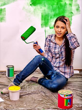 mujer sentada: Mujer feliz que se sienta en la pared de la pintura del piso en su casa. Foto de archivo