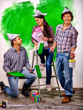 stairs interior: Happy group people paint wall on stairs at home. Stock Photo