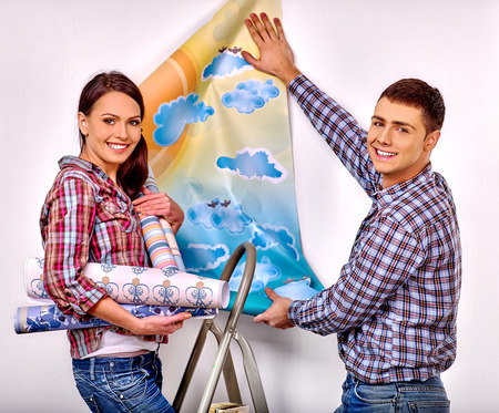 happy family at home: Happy family glues wallpaper on stairs at home.