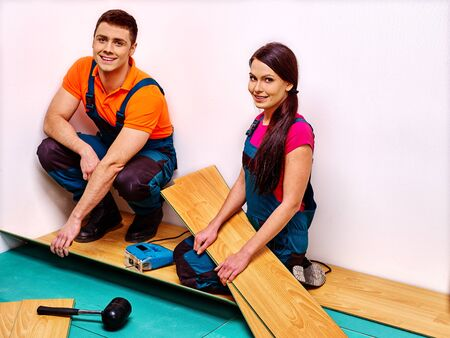 laminate flooring: Happy family sitting on floor and laying parquet at home.