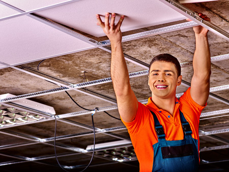 ceiling: Man in builder uniform hand up  installing suspended ceiling