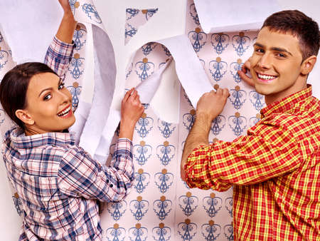 happy family at home: Happy family man and woman glues wallpaper at home. Stock Photo