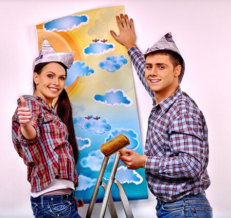 happy family at home: Happy family glues wallpaper at home.