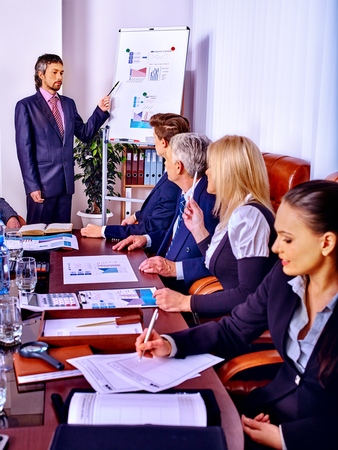 staff training: Happy group business people with chart in office. Staff training.