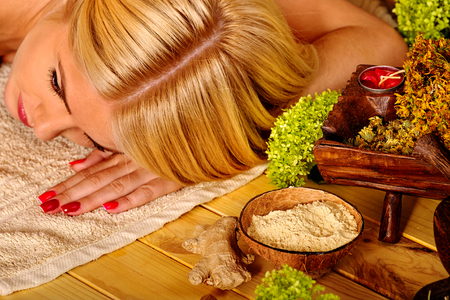 sharpness: Blond woman getting massage in tropical spa. Sharpness on spice jar. Stock Photo