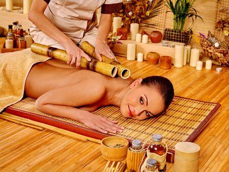 massage huile: Jeune femme obtenir un massage au bambou. Thérapeute Homme.