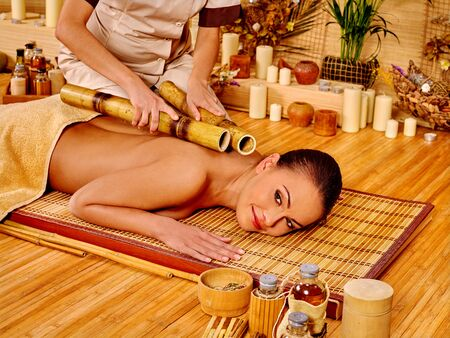 hands massage: Young woman getting bamboo massage. Male therapist.
