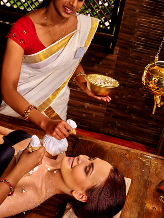 ayurvedic: Woman having ayurvedic massage with pouch of rice.