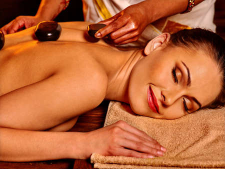 stone therapy: Young woman having Ayurveda stone massage.