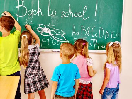 ni�os escribiendo: Los ni�os escriben en la pizarra en la escuela.
