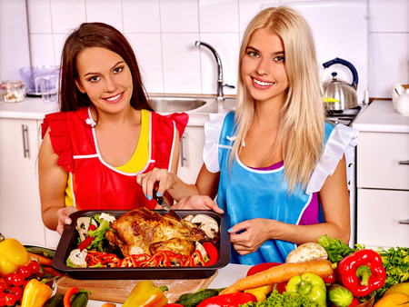PRETTY WOMEN: Happy young two pretty women cooking chicken at kitchen. Stock Photo