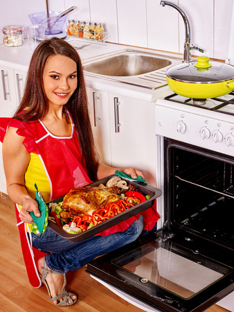 oven tray: Young woman with oven- tray cooking chicken at kitchen.