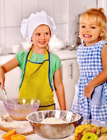 preparing dough: Children  with big metal bowl preparing  dough at kitchen. Stock Photo