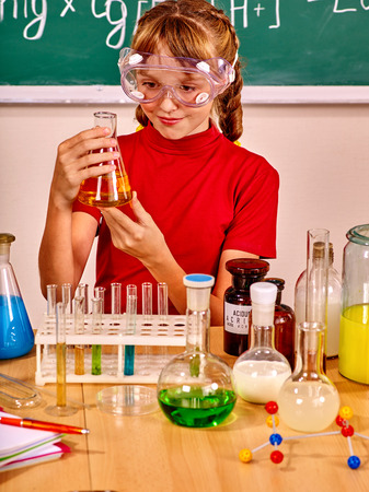 chemistry class: Child in red holding flask in chemistry class. Stock Photo