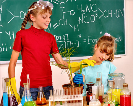 chemistry class: Children girl without teacher holding flask in chemistry class.