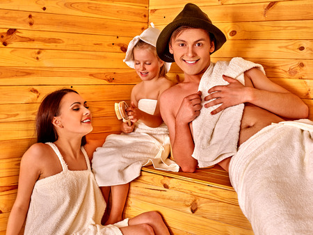 familias jovenes: Familia con un niño en el sombrero de relax. Familia sauna finlandesa