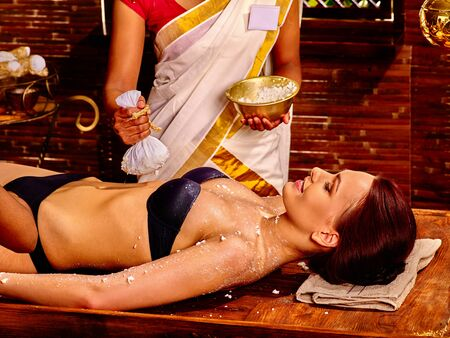 panchakarma: Woman having ayurvedic massage with pouch of rice. Spa resorts in India Stock Photo
