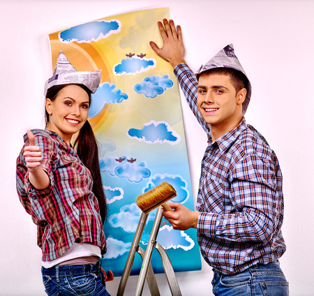 newspaper roll: Happy family glues wallpaper at home