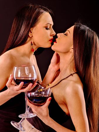 black roses: Two sexy women with red wine.Black background.