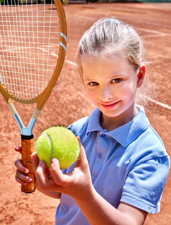 family playing: Sport kids girl with tennis racket and ball on brown court Stock Photo