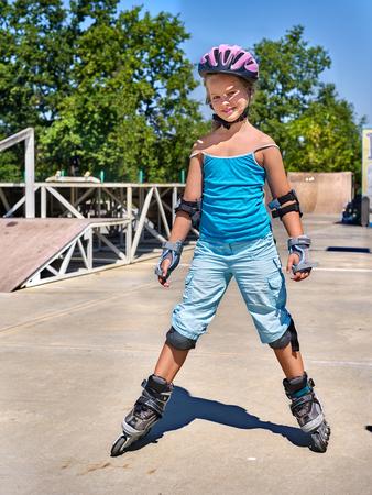 niño en patines: Muchacha que monta en patines en el parque de patinaje.