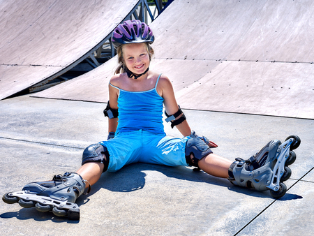 blades: Girl in roller skates sitting on ride in skatepark.