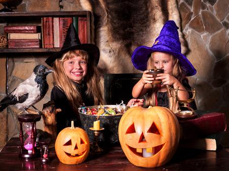 inside house: Witch  children with pumpkin lantern on Halloween.