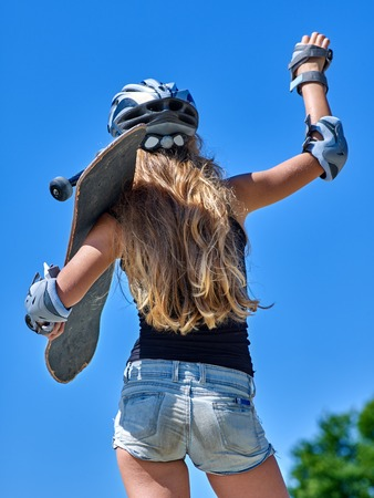 board shorts: Portrait of teen girl holding his skateboard blue sky outdoor. View from the back.