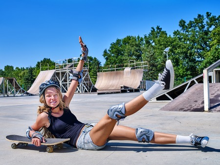 Teen girl in helmet sitting on his skateboard outdoor. Fall on person .