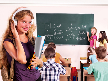 schoolkids: Group people schoolkids  in classroom. The girl in headphones on foreground. Stock Photo