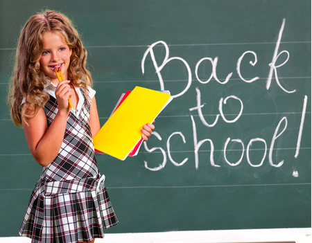 Child girl with notebook near  blackboard. Back to school.